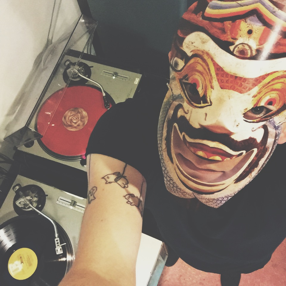 top down shot of me wearing the mask that came with Day Of The Demons and the turntable below me playing the DOTD vinyl